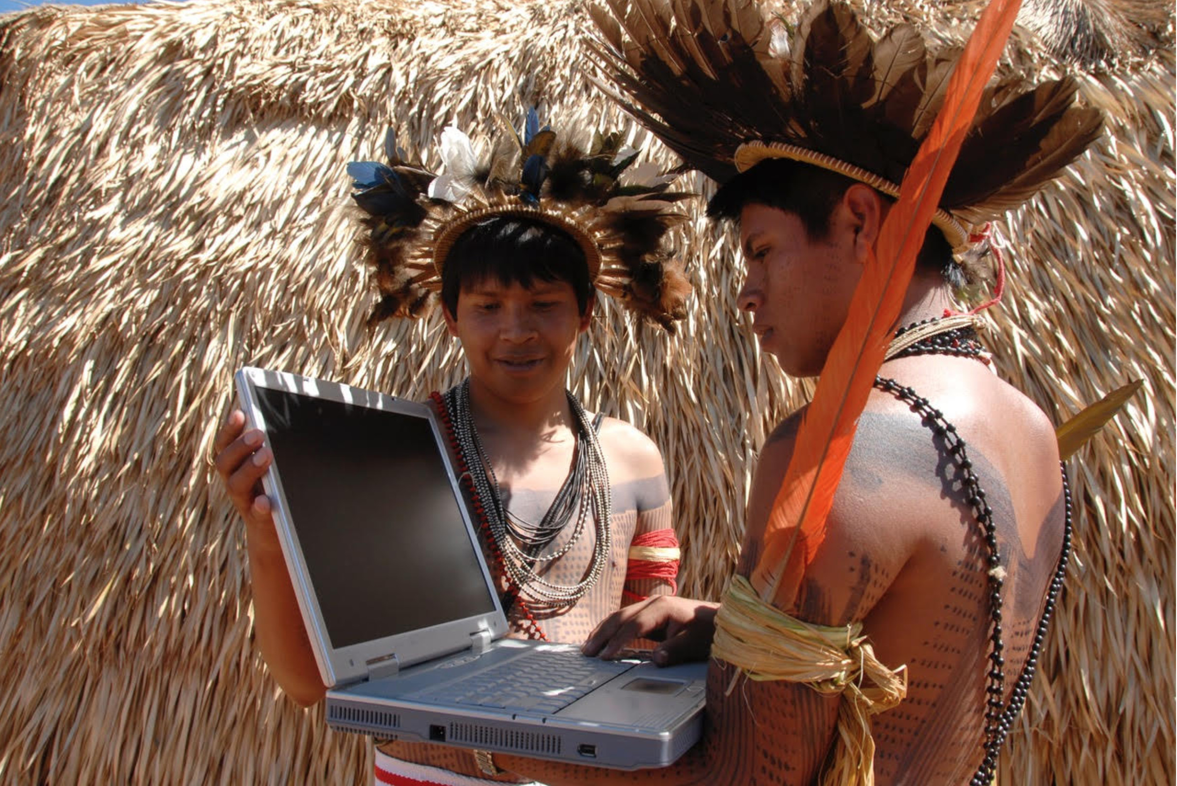 Picture shows members from the Surui Paiter Tribe in the Brazilian Amazon as they access the Internet in their remote community. Credit: Surui Metareila Association Archives. Courtesy of Vasco M. van Roosmalen from ECAM.